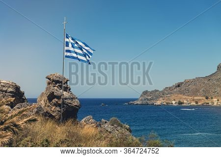Greek Flag In The Wind In A Rocky Bay