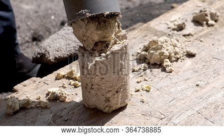A Plumber Removes Solid Deposits From Grease And Debris From A Plastic Sewer Pipe.