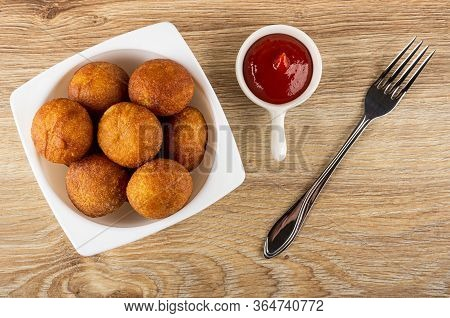 White Bowl With Small Round Fried Pies, Sauceboat With Ketchup, Fork On Wooden Table. Top View