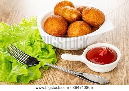 Fork On Leaves Of Lettuce, Sauceboat With Ketchup, Bowl With Small Round Fried Pies On Wooden Table