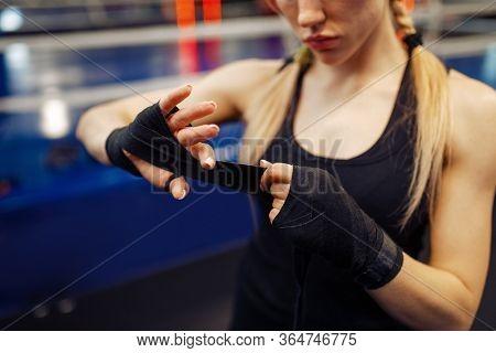 Woman winds up black bandages, boxing training