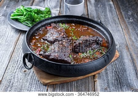 Traditional German braised beef cheeks in brown red wine sauce with carrots and broccoli offered as closeup in a modern design stewpot on an old rustic board