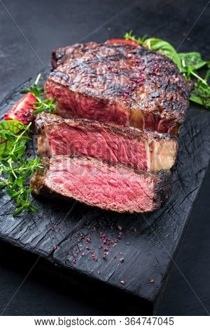 Barbecue dry aged wagyu entrecote beef steak roast with lettuce and salt as closeup on a charred wooden board