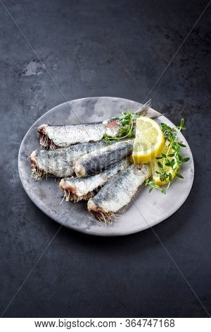 Fried sardines with lrmon slices and herbs offered as closeup on a modern design plate with copy space