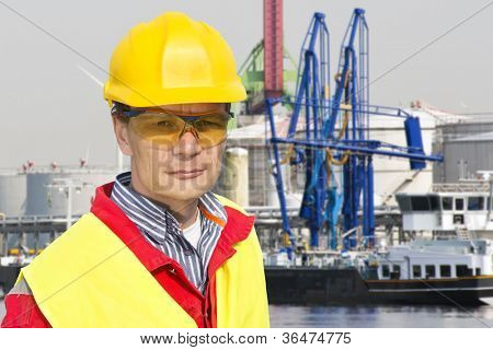 Portrait of a confident docker foreman in front of a petrochemical harbor with gas installations, numerous cranes, and a freight ship