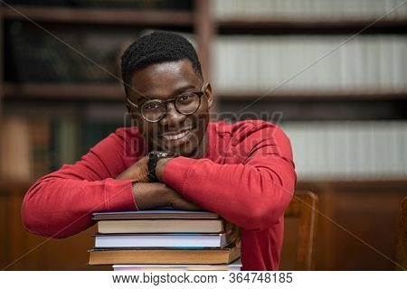 Portrait of happy african student wearing spectacles sitting in library leaning on pile of books. Smiling black young man at college library. Happy american guy at university with copy space.