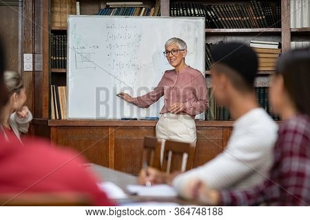 Senior teacher explaining math formulas written on whiteboard while college students sitting on table understanding the concept. Happy mature woman lecturer clearing doubts to students in class.