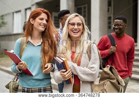 Multiethnic group of happy young women and men walking in college campus. Cheerful group of multiethnic friends feeling relaxed after university exam. Smiling classmates laughing and looking away.