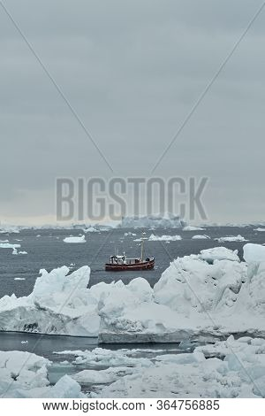 Red Classic Fishing Boat Sailing In Iceberg Filled Water