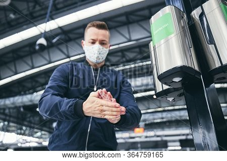 Man Wearing Face Mask And Using Hand Sanitizer At Airport. Themes Traveling During Pandemic, Hygiene