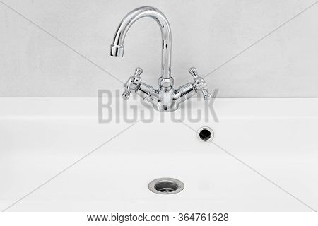 Modern Bathroom Interior With Metal Faucet And Ceramic White Sink.