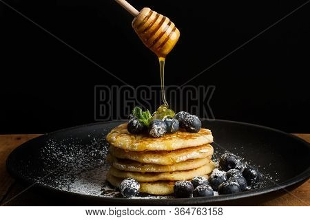 Dipping Honey On Pancakes With Blueberries On A Black Plate