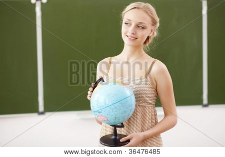 Young female teacher holding a globe at school