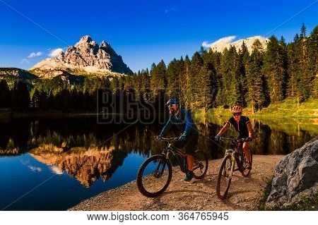 Cycling outdoor adventure in Dolomites. Cycling woman and man on electric mountain bikes in Dolomites landscape. Couple cycling MTB enduro trail track.
