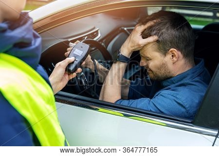 Drink And Drive Concept - Sad Drunk Man Sitting In The Car After Police Alcohol Test With Alcometer