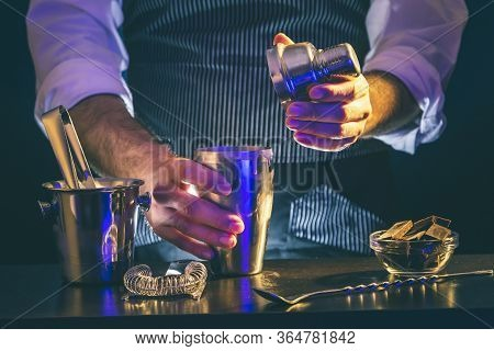 Bartender Making A Cocktail Using Cocktail Shaker, Closing The Shaker After Pouring All The Ingredie