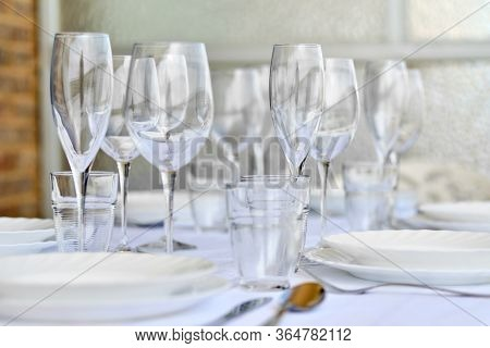 Close Up New Diverse Of Glassware And Porcelain Plates Served On White Tablecloth, No People. Table