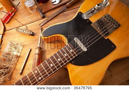Guitar on guitar repair desk. Vintage electric guitar on a guitar repair work shop. Single cutaway solid body guitar, amber color. poster