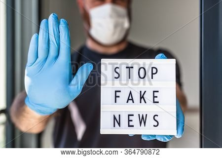 Fake News Infodemics During Covid-19 Pandemic Concept. Man Wearing Protective Mask And Medical Glove