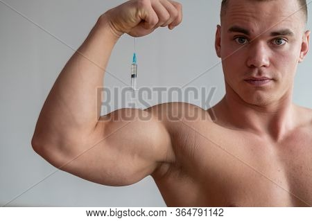 A Muscular Man With A Naked Torso Holds A Dope Syringe. Attractive Bodybuilder Puts Himself On Stero