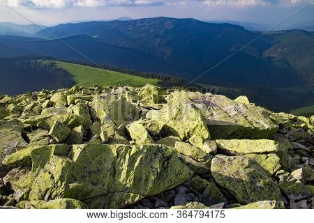 Huge Stones Covered With Green Lichen On Top Of A Mountain Against The Backdrop Of Mountains And For