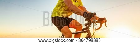 Biking cyclist riding road bike with smartwatch athlete training at sunset outdoor cycling. Sport smart watch fitness.