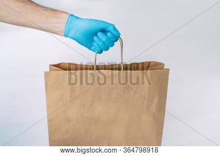 Home delivery during COVID-19 quarantine from coronavirus self isolation lockdown. Grocery store shopping delivery man giving paper bag wearing blue glove as protection for Corona virus prevention.