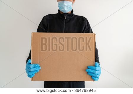 Online food delivery man delivering at home door cardboard box parcel wearing protective glove and mask ppe prevention for COVID-19.