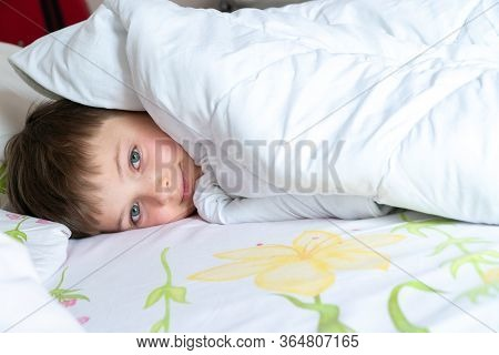 Top View Of Little Boy In Bed Covering His Face With White Blanket Or Coverlet. Sleeping Boy.