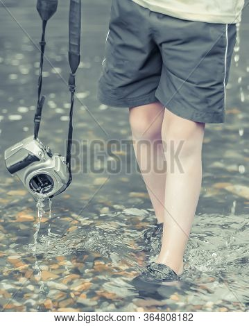 A Kid Stands In The River On Outdooor And Destroys A Mirrorless Camera. The Concept Of Obsolescence