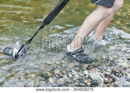 A Schoolboy Stands In The River On Outdooor And Destroys A Mirrorless Photo Camera. The Concept Of O