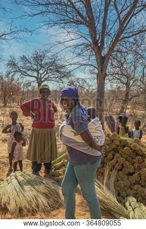 African mother carry child in the back, villagers and granny, in a rural area in her village in Botswana
