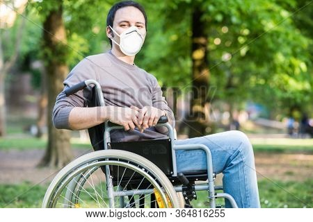 Portrait of a masked man on a wheelchair in a park during coronavirus pandemic