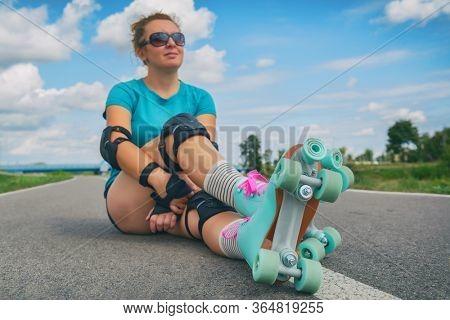 Woman in a vintage roller skates, retro quad roller skates sitting outdoors.
