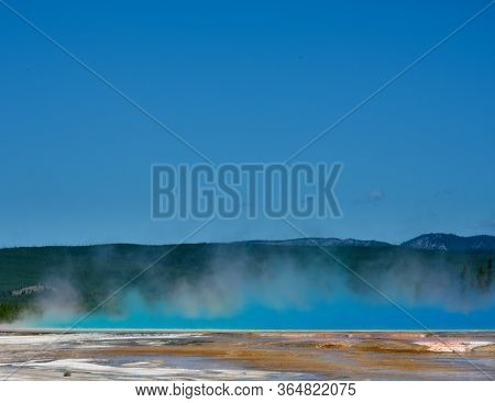 Grand Prismatic Color Bleeds Into Steam In Yellowstone Mountains