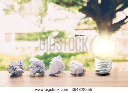 Idea And Inspiration Concept With Paper Crumple And Light Bulb On Table About Success, Creative And