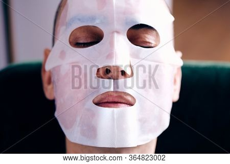 closeup of a handsome caucasian man wearing a bio-cellulose sheet mask at home