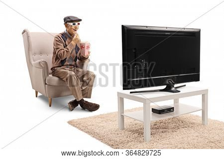 Elderly man seated in an armchair eating popcorn and watching a 3d movie isolated on white background