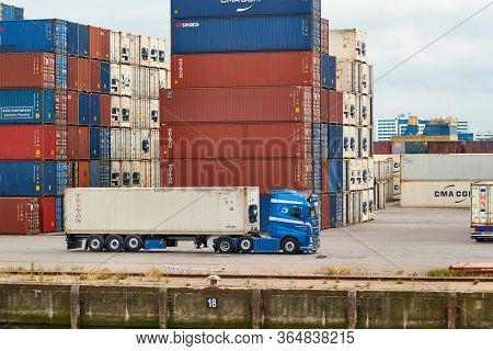 ROTTERDAM, THE NETHERLANDS - CIRCA 2019: Cargo container stacks, semi truck in an intermodal shipping hub, container terminal, Waalhaven harbor of the Port of Rotterdam, biggest cargo port in Europe