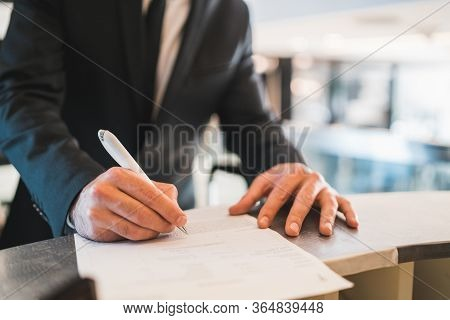 Portrait Of Businessman Check-in At Hotel Reception Front Desk. Business Travel Concept.