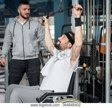 Disabled man in wheelchair working out with coach