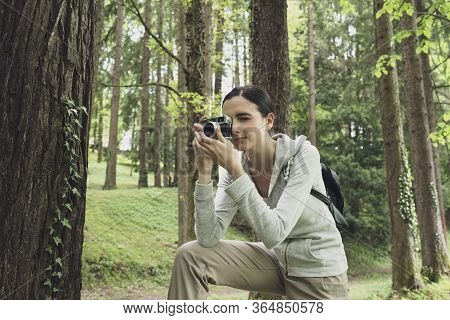 Young Woman Walking In Nature And Taking Pictures