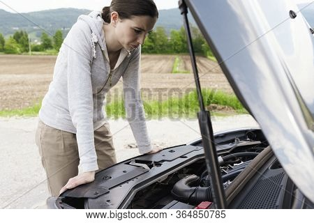 Woman Having A Car Breakdown And Staring At The Engine