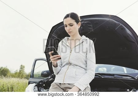 Woman Leaning On The Car And Calling A Car Repair Service