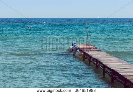 Antique Wooden Boardwalk Over Blue And Azure Sea. Small Waves With Calm Sea. Some Boats In The Dista