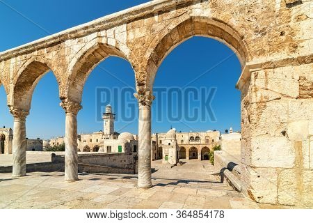 View of typical houses and minaret under blue sky through ancient stone arches on Temple Mount in Old City of Jerusalem, Israel.