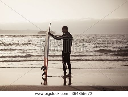 Rear View Of Strong Surfer With Surfboard On The Beach At Sunset Or Sunrise.