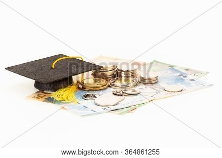 Education Costs Concept With Mortar Board And  Coins On Top Of Banknotes