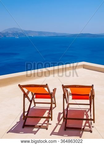 Two Chairs On Terrace And Amazing Santorini Volcano View. Santorini, Cyclades, Greece.