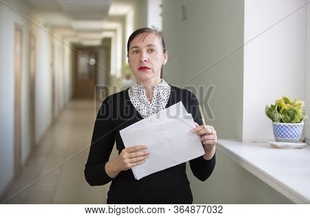 Woman With Papers At The Office. Co-worker In The Hallway